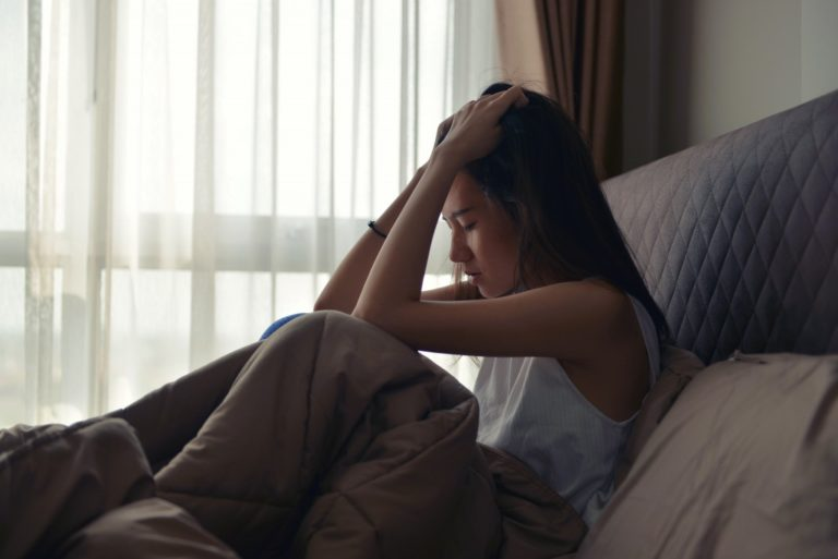 woman sitting in a bed feeling so down