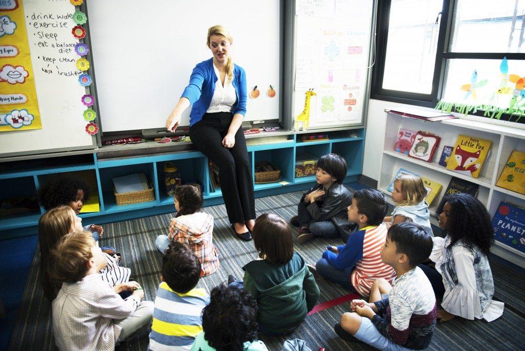 preschool teacher picking a student to recite in her class