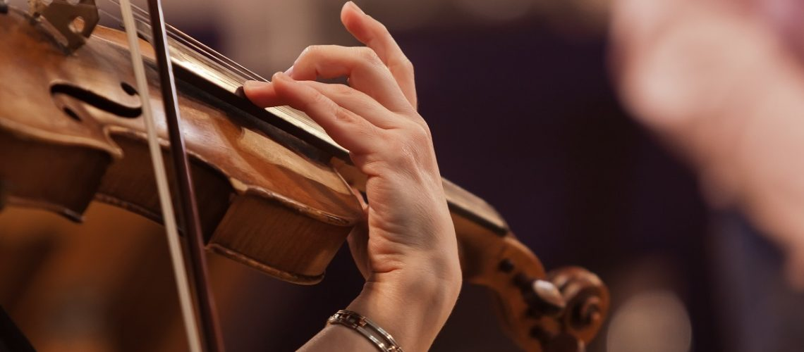 hands on the string of a violin